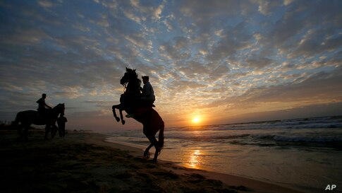 Palestinians rides horses on Gaza beach as the sun sets in Gaza City.