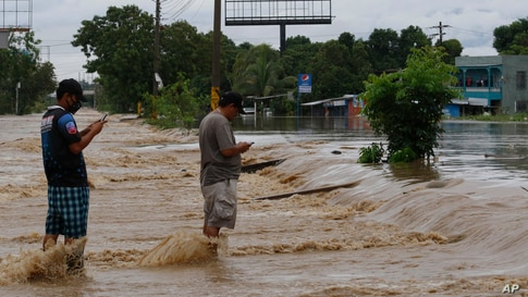 Men check their cell phones in the middle of a flooded street after the passing of Hurricane Iota in La Lima, Honduras.