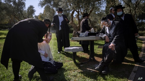Ultra-Orthodox Jewish men are covered with flour after being pepper sprayed by security guards during a protest against the construction of a hotel at a site that protesters claim contains ancient graves, in Jerusalem.