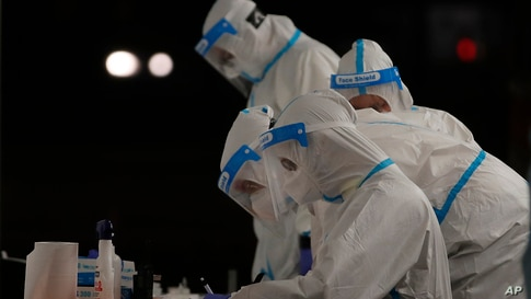 Medical staffers wearing protective suits work at a triage check point that was set to ease the pressure on hospital emergency wards, following the surge of COVID-19 case numbers, in Milan, Italy.
