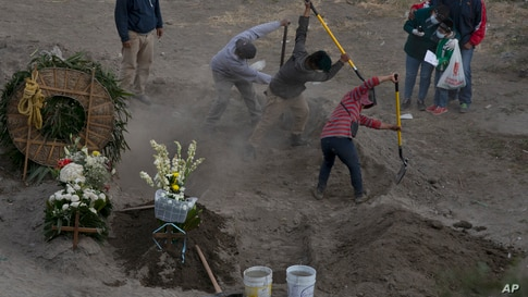 Workers bury 86-year-old Gabina Salgado Husca, who died of complications related to the COVID-19, in the Valle de Chalco municipal cemetery on the outskirts of Mexico City, Nov. 18, 2020.