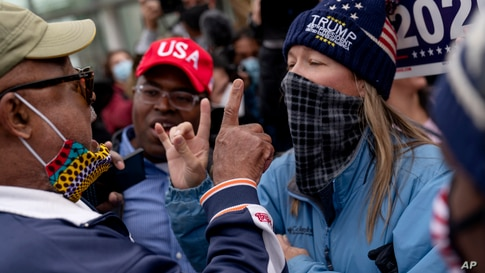 U.S. President Donald Trump's supporters, right, argues with a counter protester, left, as they protest election results outside the central counting board at the TCF Center in Detroit, Michigan.