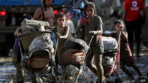 Children push baby strollers full of belongings they retrieved from their homes damaged by Typhoon Vamco in Rodriguez, Rizal province, Philippines.