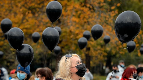 Medical workers hold black balloons in memory of those who lost their lives while in the care of the state health system in Bucharest, Romania.