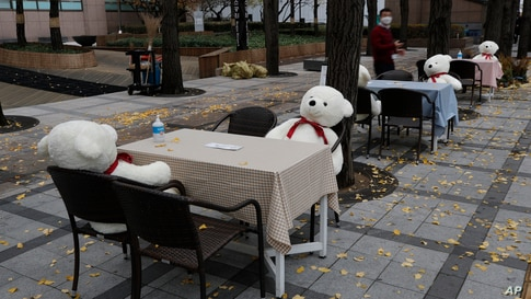 Tables and chairs are placed with hand sanitizers and stuffed toys while maintaining social distancing in downtown Seoul, South Korea.