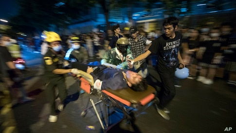Pro-democracy protesters help to move a protester with gun-shot injuries during an anti-government rally outside the Parliament in Bangkok, Thailand.