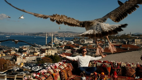 A seagull files over a man sitting at a coffee shop backdropped by the Bosporus Strait in Istanbul, Turkey.