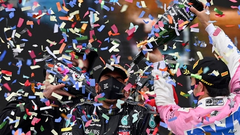 Second placed Racing Point driver Sergio Perez of Mexico, right, pours champagne on winner Mercedes driver Lewis Hamilton of Britain on the podium of the Formula One Turkish Grand Prix at the Istanbul Park circuit racetrack in Istanbul, Turkey.