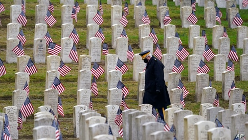 Retired U.S.Army veteran Bill MacCully walks among flag-covered graves in the Veterans Cemetery of Evergreen Washelli Memorial Park on Veterans Day in Seattle, Washington.