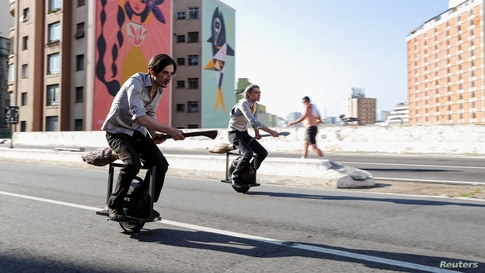 Vinicius Sanctus and Alessandro Russo ride electric monowheels called 'nuvem' (cloud) in Sao Paulo, Brazil. Their invention was inspired by the magic flying brooms of the Harry Potter series.