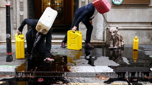 Activists from the climate action group Ocean Rebellion perform a stunt outside The Baltic Exchange building, in London.