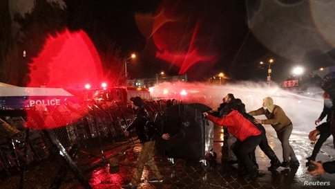 Demonstrators react as riot police use a water cannon during an opposition rally against the results of a parliamentary election, outside the Central Election Commission (CEC) building in Tbilisi, Georgia, Nov. 8, 2020.