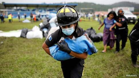 A firefighter carries a baby rescued along with her mother from an area affected by mudslides caused by Storm Eta, in San Cristobal Verapaz, Guatemala, Nov. 7, 2020.
