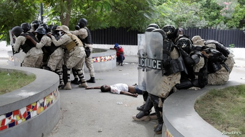 Haitian National Police (PNH) officers take position next to a dead body during clashes with protesters during a demonstration demanding the resignation of President Jovenel Moise in Port-au-Prince, Nov. 18, 2020.