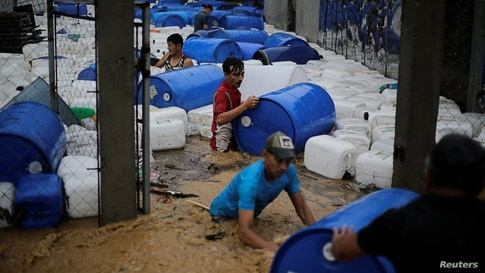 Men recover plastic barrels from a business affected by a flooding caused by rains from Storm Eta, in Toyos, Honduras, Nov. 4, 2020.