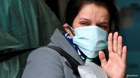 A woman possibly suffering with COVID-19 waves goodbye to her family inside an ambulance before being transported to a hospital in Arcore, near Monza, Italy.
