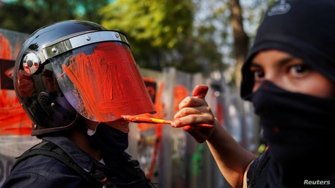 A member of a feminist collective paints the helmet of a riot police officer during a protest against gender and police violence, in Mexico City, Mexico, Nov. 11, 2020.