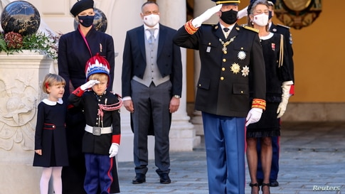 Prince Albert II and Prince Jacques salute as Princess Charlene and Princess Gabriella watch during celebrations marking Monaco's National Day at the Palace.