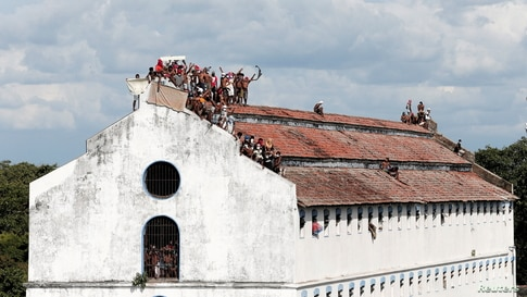 Inmates protest on the top of a prison building demanding to speed up their judicial process and that they be granted bail, after the number of COVID-19 cases increased in prisons in Colombo, Sri Lanka.