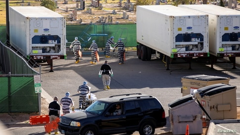 El Paso County detention inmates help move bodies of people who died of COVID-19 to refrigerated trailers outside the Medical Examiner's Office in El Paso, Texas, Nov. 14, 2020.