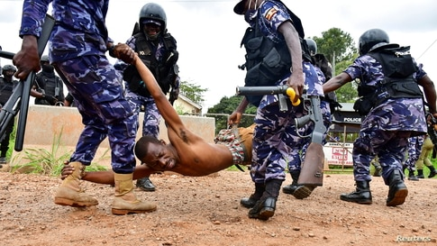 Riot policemen detain a supporter of presidential candidate Robert Kyagulanyi, also known as Bobi Wine, in Luuka district, eastern Uganda.