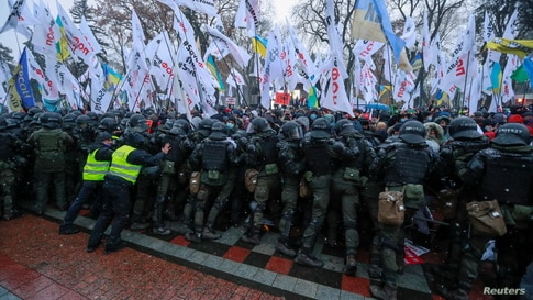 Ukrainian law enforcement officers block demonstrators during a rally held by entrepreneurs and representatives of small businesses near the parliament building amid the COVID-19 outbreak in Kyiv.