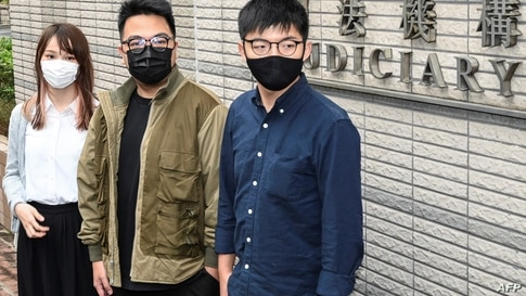 (FILES) In this file photo taken on November 23, 2020 Pro-democracy activists (L-R) Agnes Chow, Ivan Lam and Joshua Wong arrive…