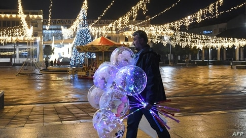 A man walks holding baloons on an almost deserted Podgorica's central square on New Year's Eve on December 31, 2029, as…