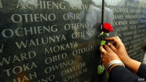 Kenyan residents put flowers  07 August, 2002 in front of the memorial  with the names of the people who died during the 1998…