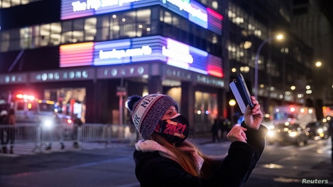 A woman wearing a protective mask takes a photo outside Times Square during the virtual New Year's Eve event following the…