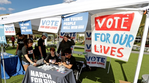 FILE - Student volunteers help out at a booth to encourage on campus voting for students.