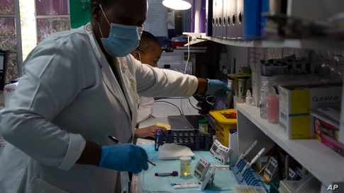 Laboratory technicians test a blood sample for HIV infection at the Reproductive Health and HIV Institute (RHI) in Johannesburg, Nov. 26 2020.