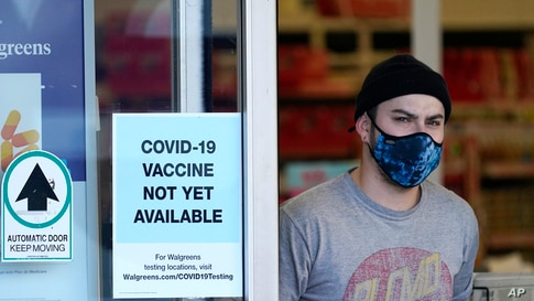 Customer wearing mask walks out of Walgreen's pharmacy store and past sign advising that COVID-19 vaccines are not available.