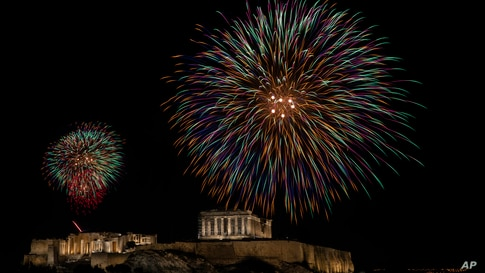 Fireworks explode over the ancient Parthenon temple at the Acropolis hill during the New Year's Eve celebrations in Athens,…