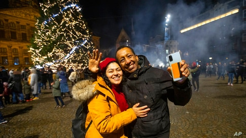 People celebrate New Year in front of the Royal Palace, rear left, in Amsterdam, Netherlands, Friday, Jan. 1, 2021. As the…
