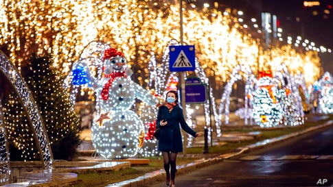 A woman runs by holiday season decorations near the parliament, a traditional place for street celebrations on New Year's eve…