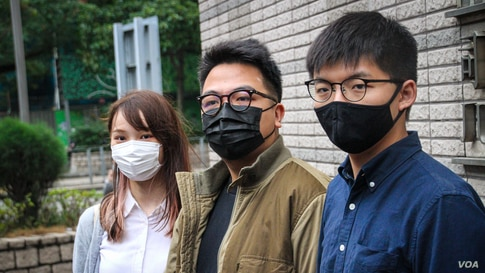 Agnes Chow, left, Ivan Lam, center, and Joshua Wong are seen outside West Kowloon Court, Hong Kong, Nov. 23, 2020. All were sentenced to jail Dec. 2, 2020. (Tommy Walker/VOA)