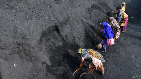 Workers load up coal into baskets in Dhaka, Bangladesh.