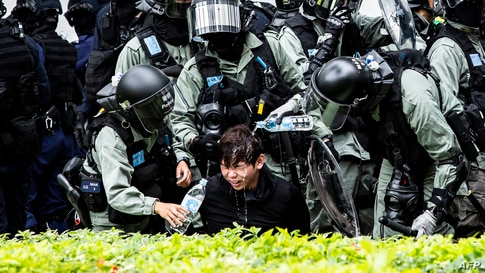 A proteste has pepper spray washed from his his face by police after being detained during a clearance operation after a demonstration against parallel trading in Sheung Shui in Hong Kong, Jan. 5, 2020.