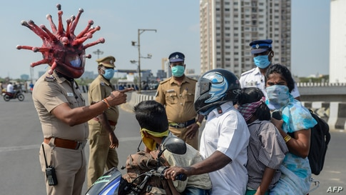 Police inspector Rajesh Babu (C) wearing a coronavirus-themed helmet speaks to a family on a motorbike at a checkpoint during a government-imposed nationwide lockdown in Chennai, India, March 28, 2020.