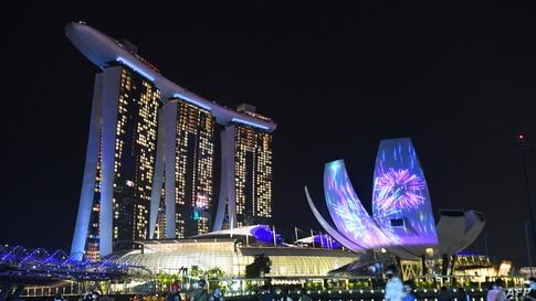 People watch as the Marina Bay area is lit up as part of New Year's Eve celebrations in Singapore, Dec. 31, 2020.