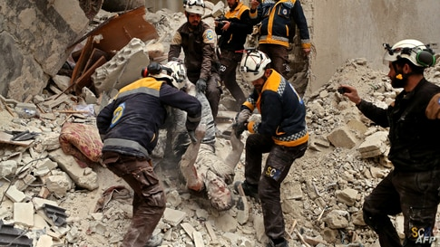 Members of the White Helmets remove the body of a victim from the rubble of a building, hit during an airstrike by government forces on the rebel-held town of Ariha in Syria's Idlib province, Feb. 5, 2020.