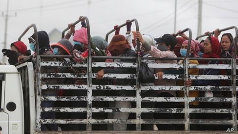 FILE - Garment workers stand on the cargo platform of a truck as they head home after their work shift outside Phnom Penh, Cambodia, Nov. 11, 2020.