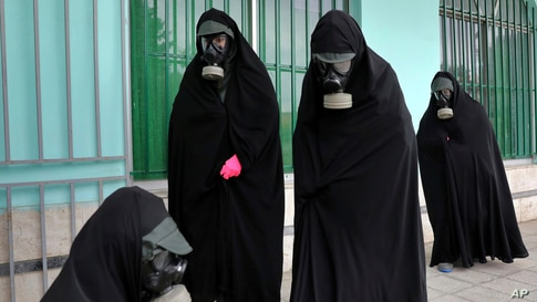"""Women clerics wearing protective clothing and """"chador,"""" a head-to-toe garment, arrive at a cemetery to prepare the body of a person who died from COVID-19 for a funeral, in Ghaemshahr, Iran, April 30, 2020."""