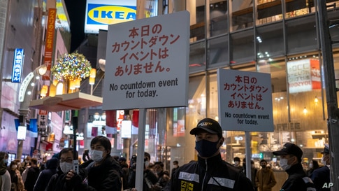 Police officers hold up signs as people arrive at Shibuya crossing, a popular location for New Year's Eve gathering, Dec. 31, 2020, in Tokyo, Japan.