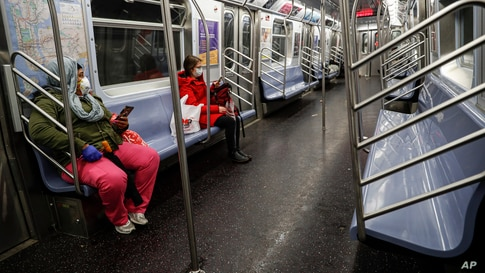 Subway riders wear protective masks and gloves on a sparsely populated car during morning hours due to COVID-19 concerns that are driving down ridership, March 19, 2020, in New York.