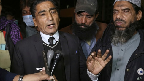 Lawyer Nadeem Ahmed Azar, L, and Sheikh Muhammad Aslam, brother of British-born Pakistani Ahmed Omar Saeed Sheikh, who is charged in the murder of American journalist Daniel Pearl, talks to media outside a prison in Karachi, Pakistan, Dec. 24, 2020.