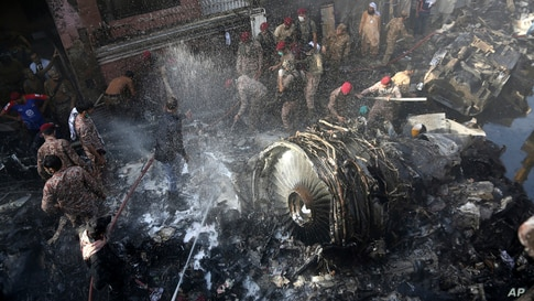 Rescue workers and local residents search for survivors in the wreckage of a plane that crashed with nearly 100 people onboard in a residential area of Karachi, Pakistan, May 22, 2020.