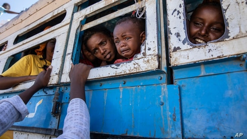Tigray refugees who fled the conflict in the Ethiopia's Tigray, ride a bus going to the Village 8 temporary shelter, near the Sudan-Ethiopia border, in Hamdayet, eastern Sudan.