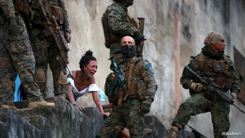 A woman reacts next to the body of a person who was shot near Sao Carlos slums complex during a police operation after heavy confrontations between drug gangs in Rio de Janeiro, Brazil, Aug. 27, 2020.
